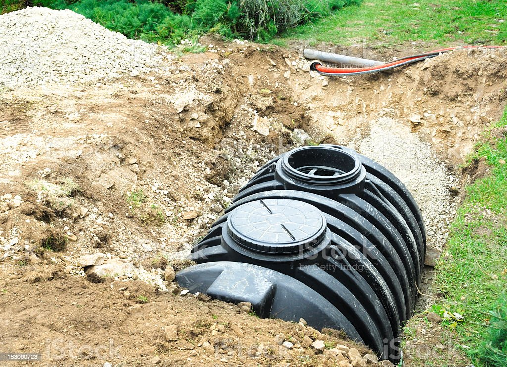 A black septic tank halfway buried in dirt outside stock photo
