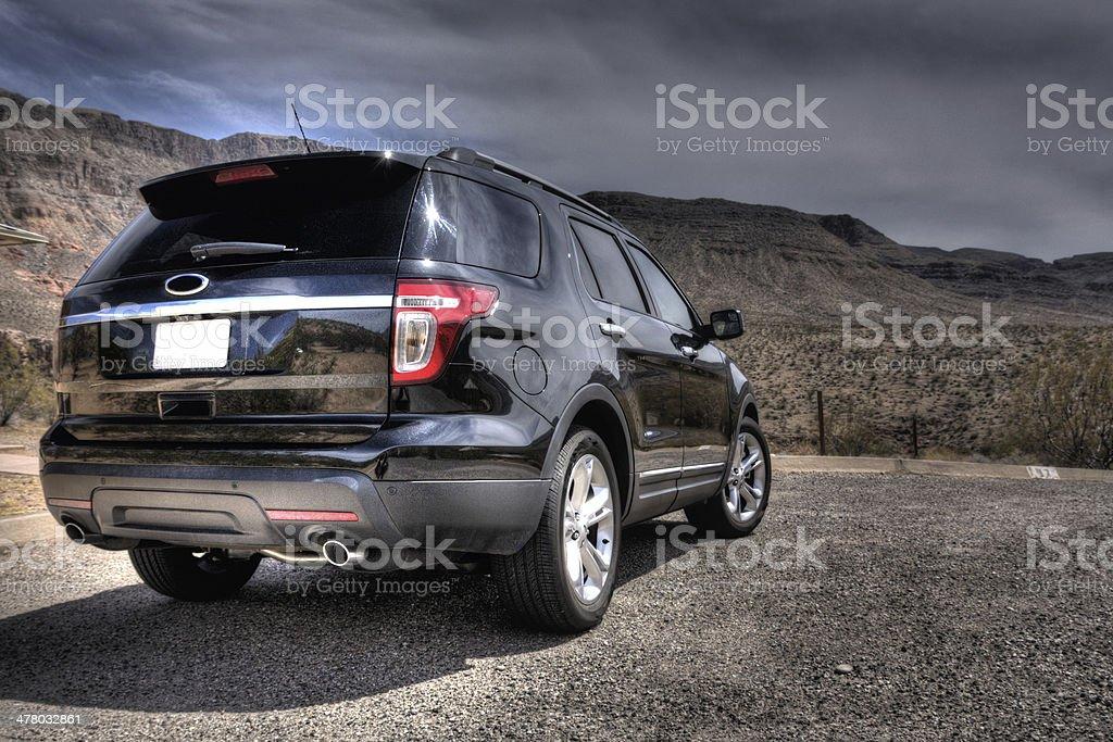 Black, shiny SUV in desert stock photo