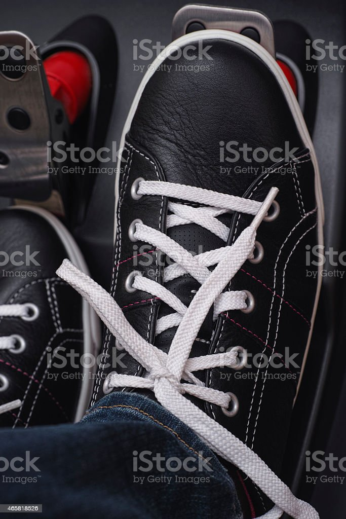 Black shoe pushing on the gas pedal in a car  stock photo