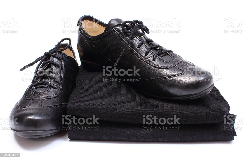 Black shoes on stack of womanly clothes. White background stock photo