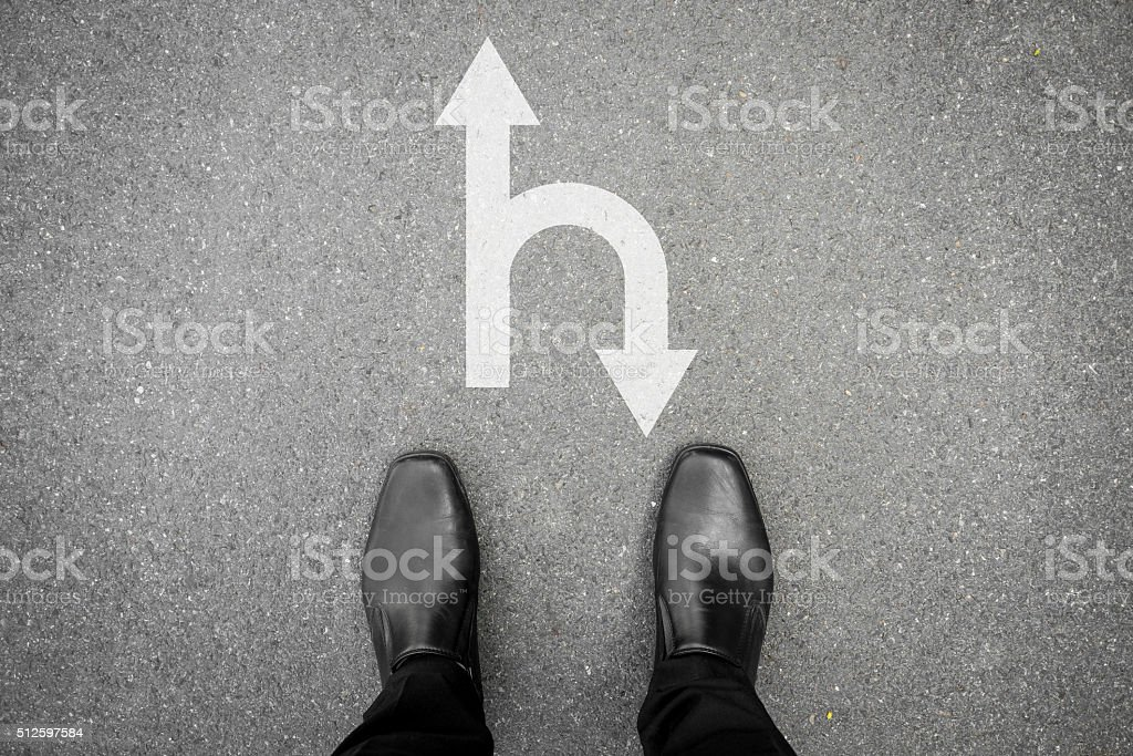 Black shoes standing at the crossroad - forward or backward stock photo
