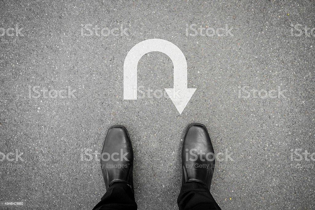 Black shoes standing in front of u turn symbol stock photo