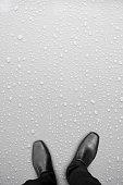 Black shoes standing on white wet floor
