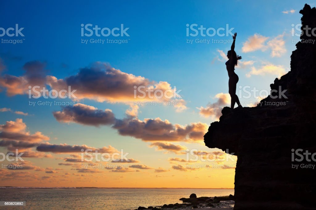 Black silhouette of happy woman on sunset background stock photo