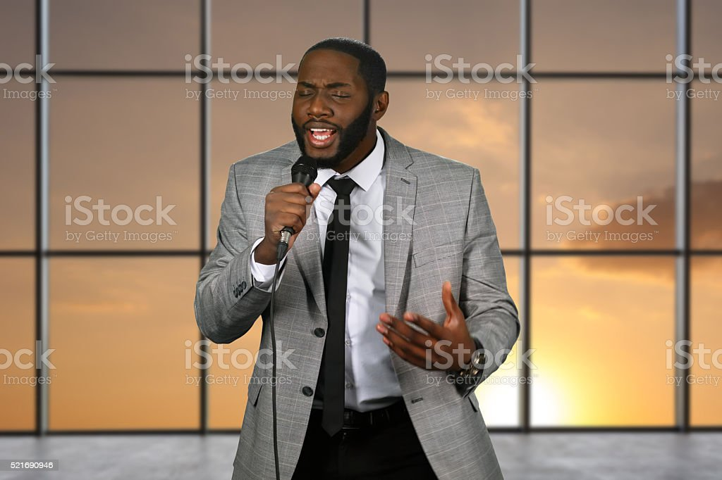 Black singer holding microphone. stock photo