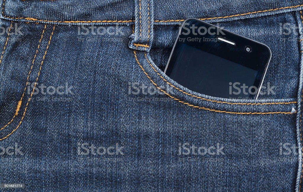 Black smartphone in your pocket jeans. background. stock photo