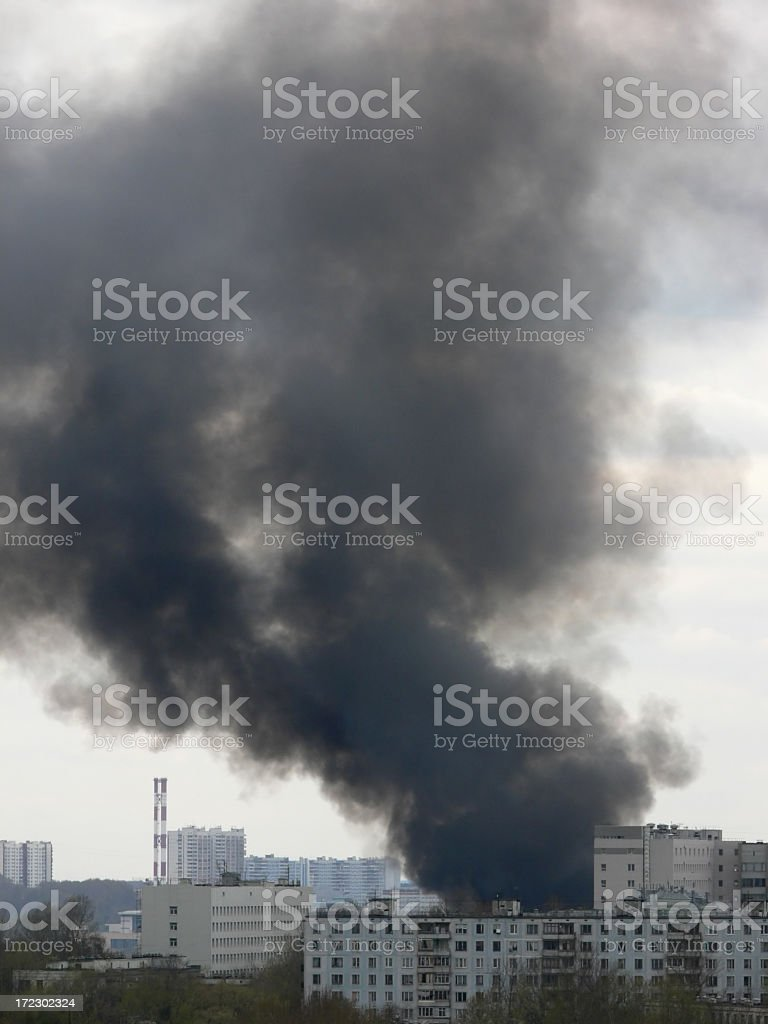Black smoke coming out of a building on fire stock photo