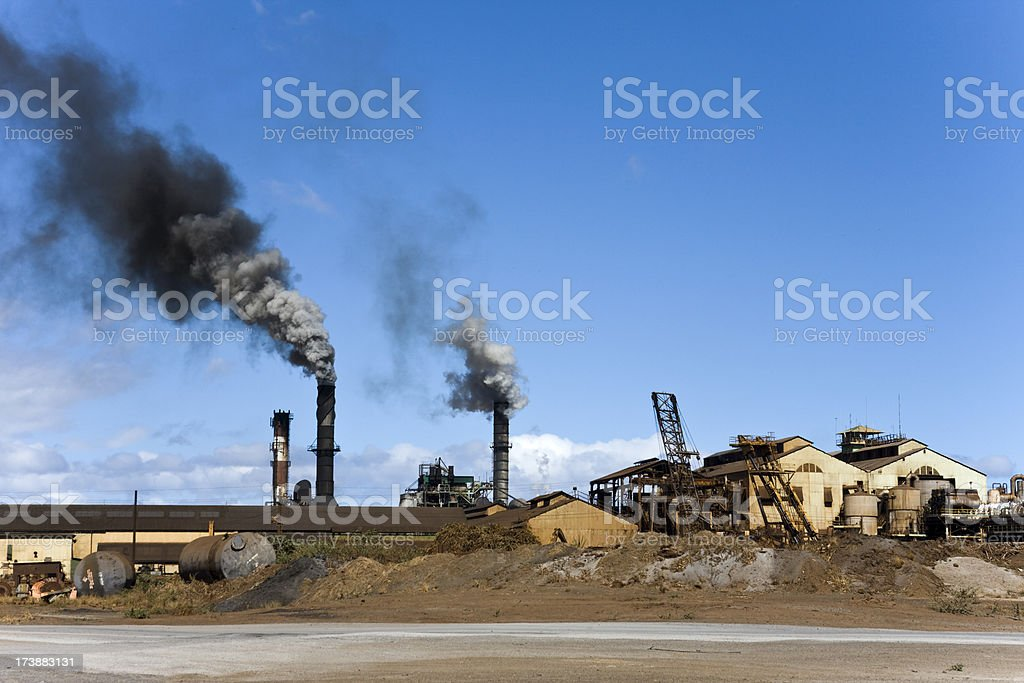 Black Smoke rising from run down looking Industrial Plant royalty-free stock photo