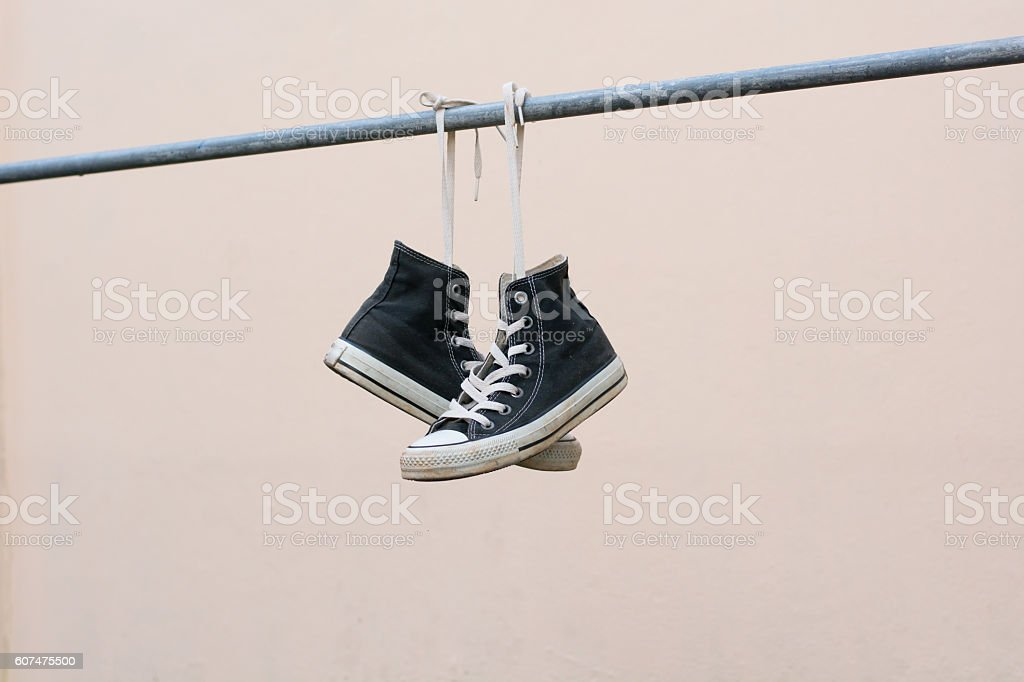 Black sneakers hanging on metal bar stock photo