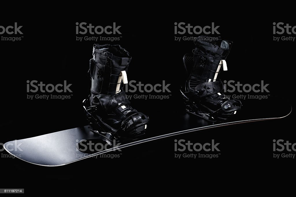 Black snowboard with bindings and boots isolated on black. stock photo