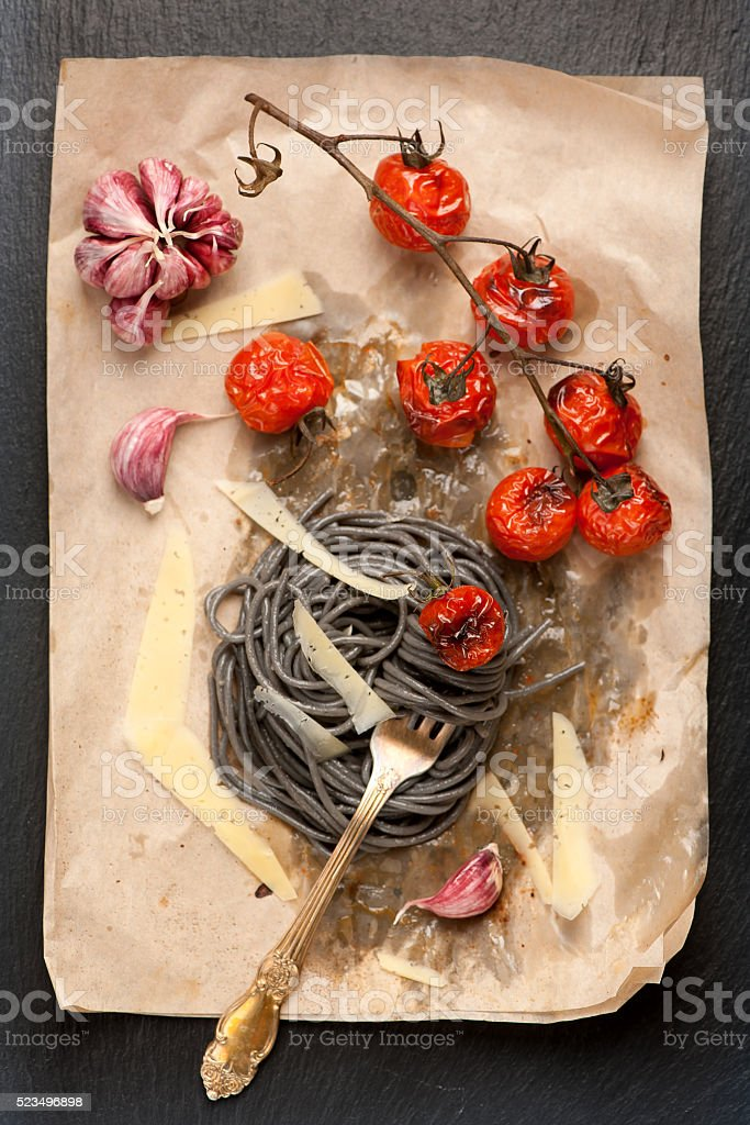 Black Spaghetti with baked tomatoes and parmesan cheese. stock photo