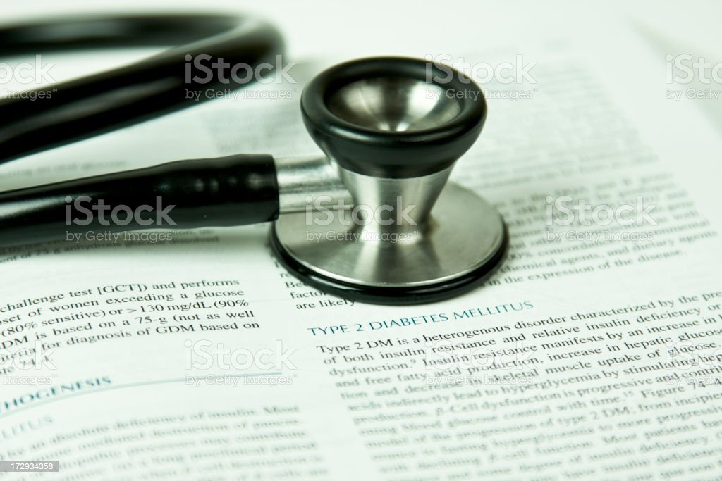 A black stethoscope lying on a book royalty-free stock photo