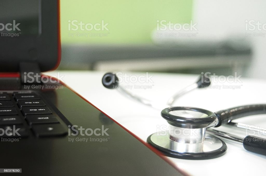 Black stethoscope next to a laptop stock photo