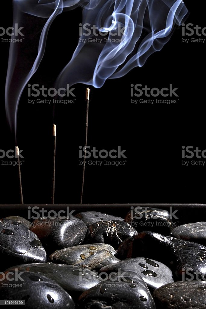 Black stones and incense stick royalty-free stock photo