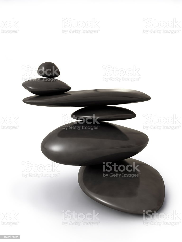 Black stones stacked and balancing on white background royalty-free stock photo