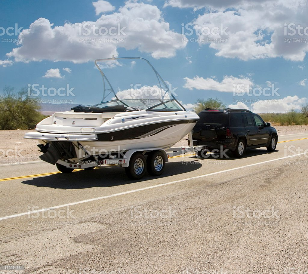 A black SUV is hauling a white motor boat for boating trip stock photo
