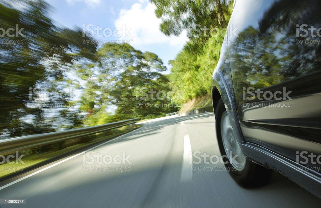 Black SUV speeding down narrow curved road stock photo