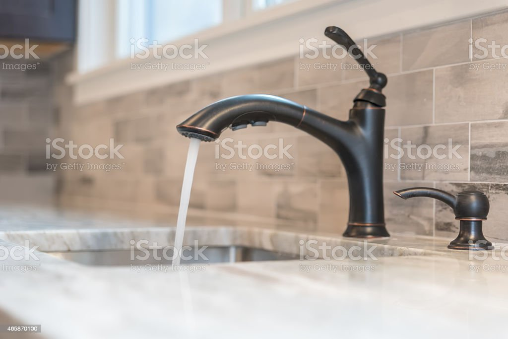 A black tap pouring water into a sink stock photo