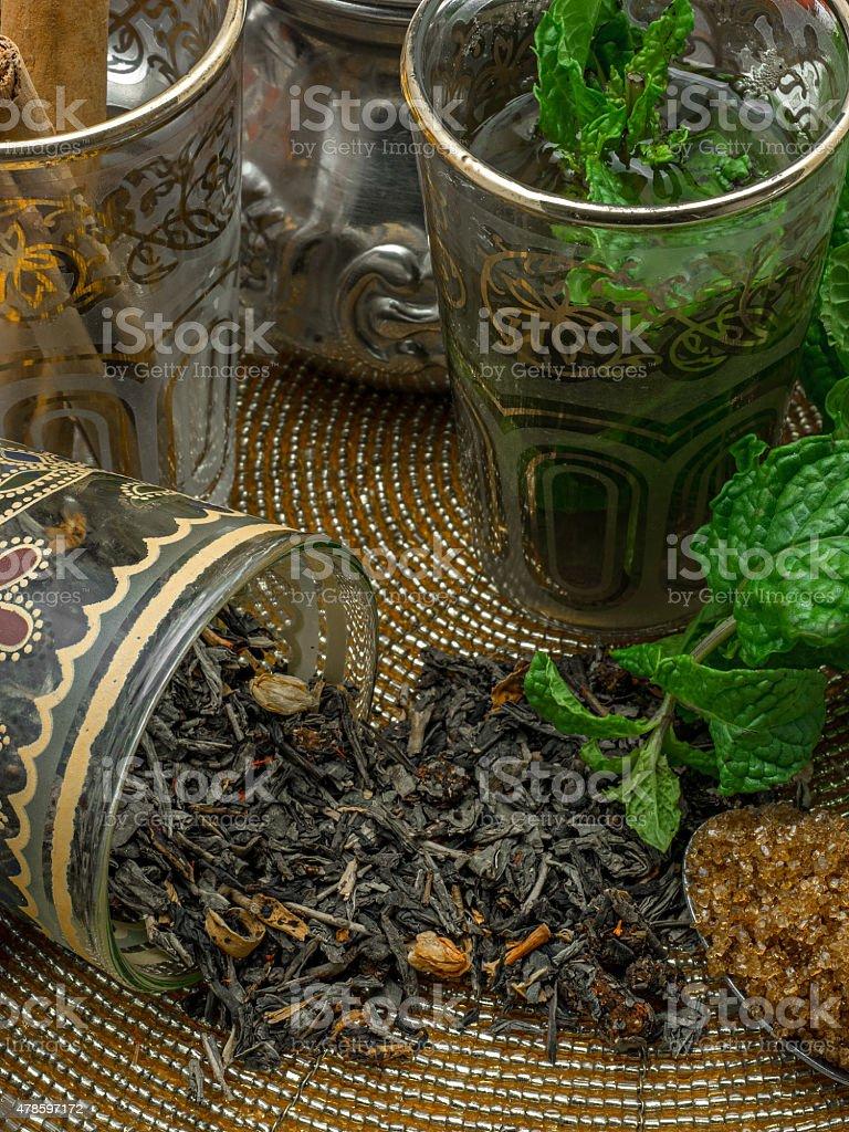 Chá preto, servidos em uma taça de cristal, folhas de hortelã, secas e chá. foto royalty-free