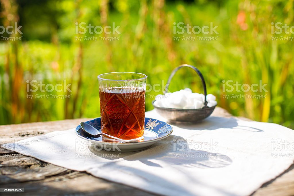 Black tea in crystal glass with blue saucer stock photo