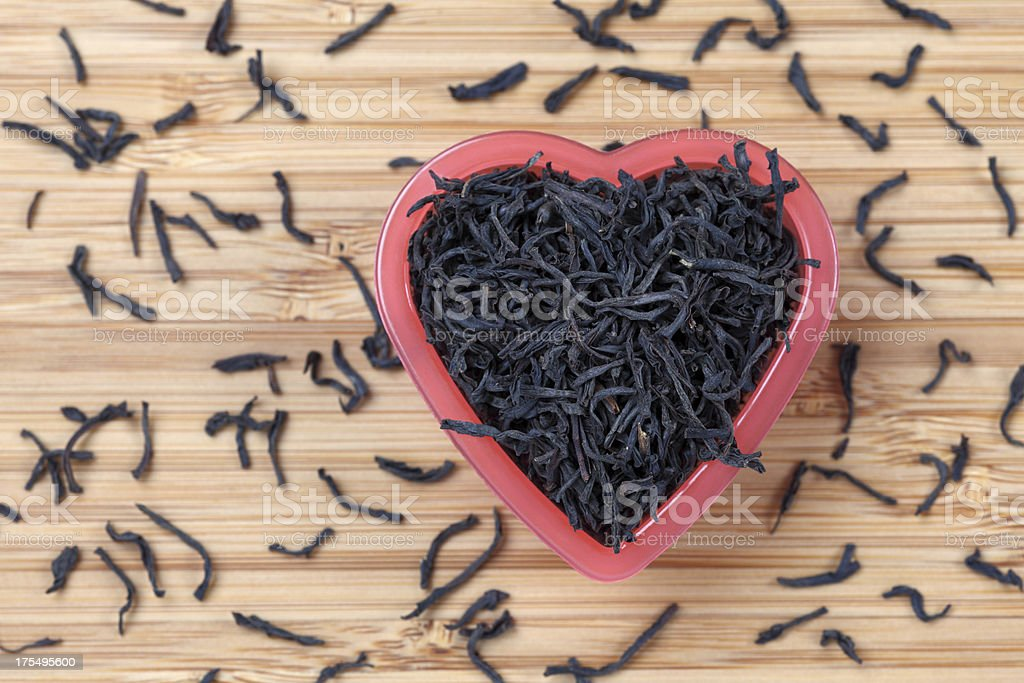 Black tea leaves in a heart bowl royalty-free stock photo