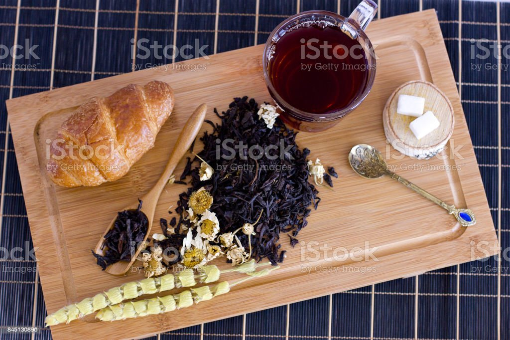 Black tea with chamomile, sage and croissant on wooden tray stock photo