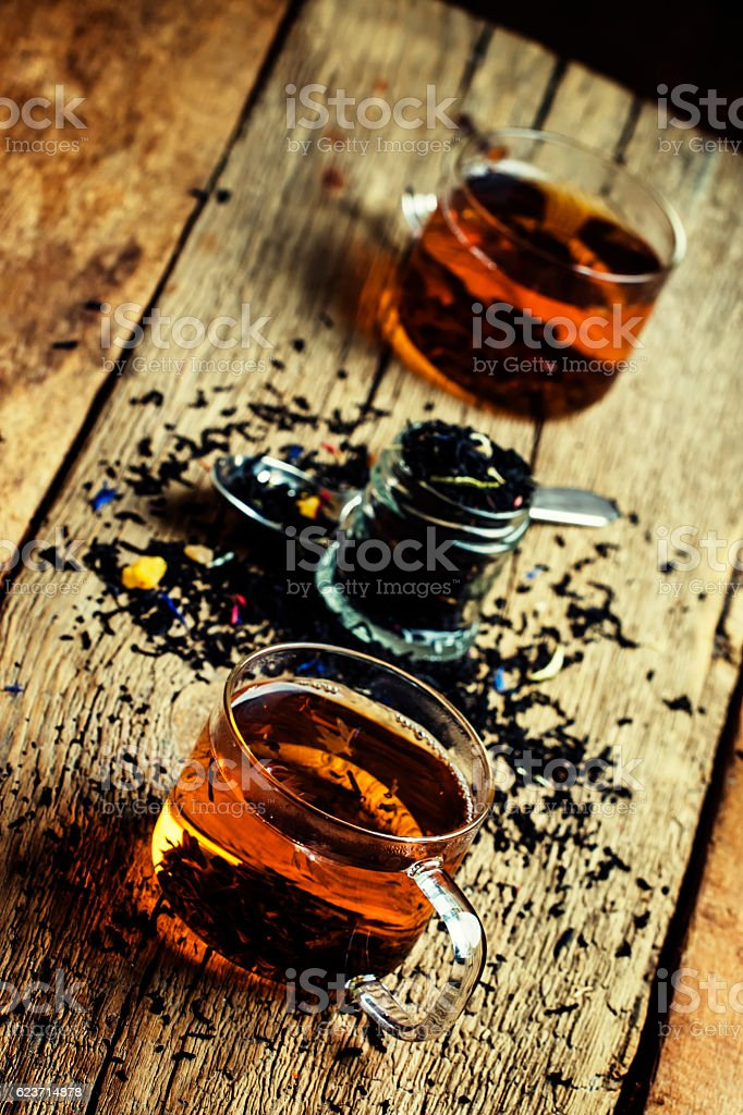 Black tea with flowers cornflower and dried fruit stock photo