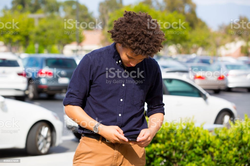 Black Teen On Cell Phone In Front of Cars stock photo