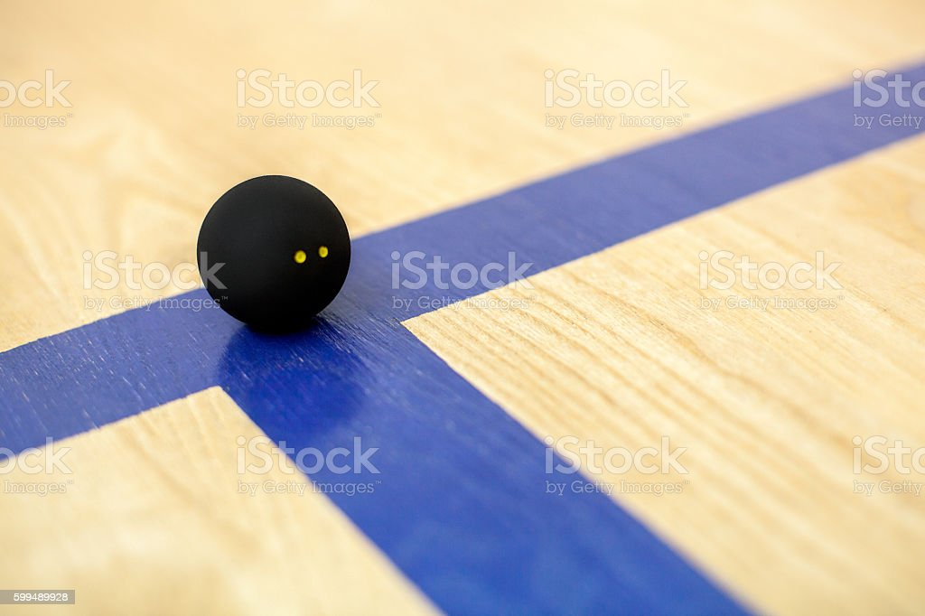 Black tennis ball is lying on wooden court stock photo