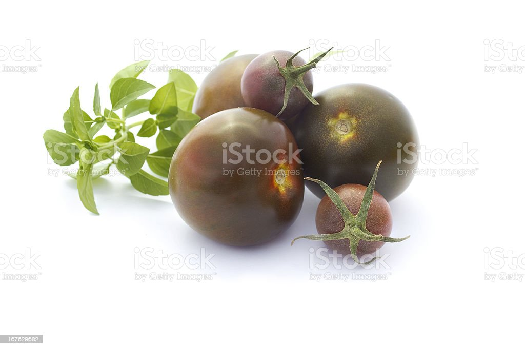 Black tomatoes and basil isolated on white stock photo