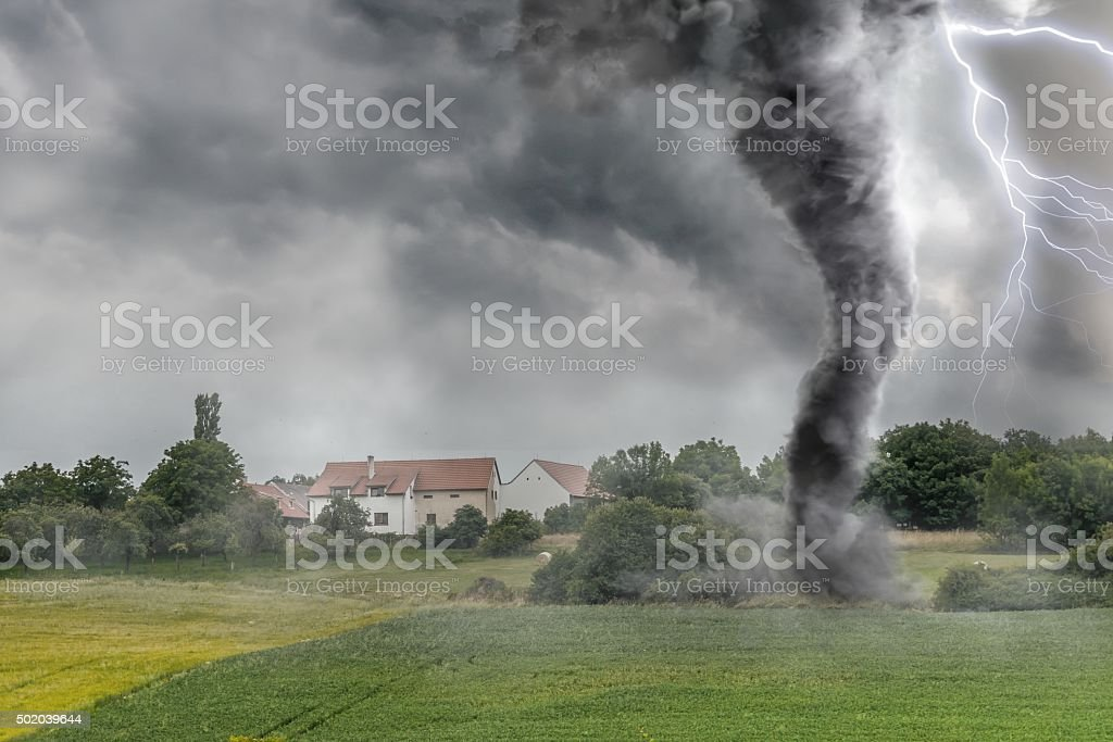 Black tornado funnel and lightning over field during thunderstor stock photo