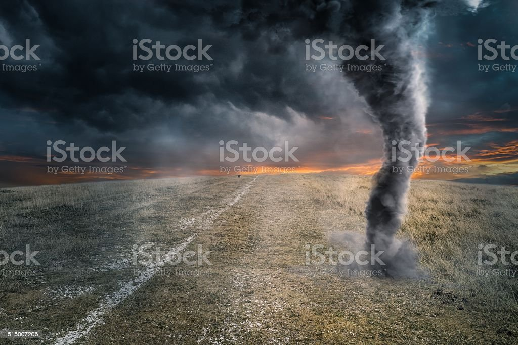 Black tornado funnel over field during thunderstorm stock photo