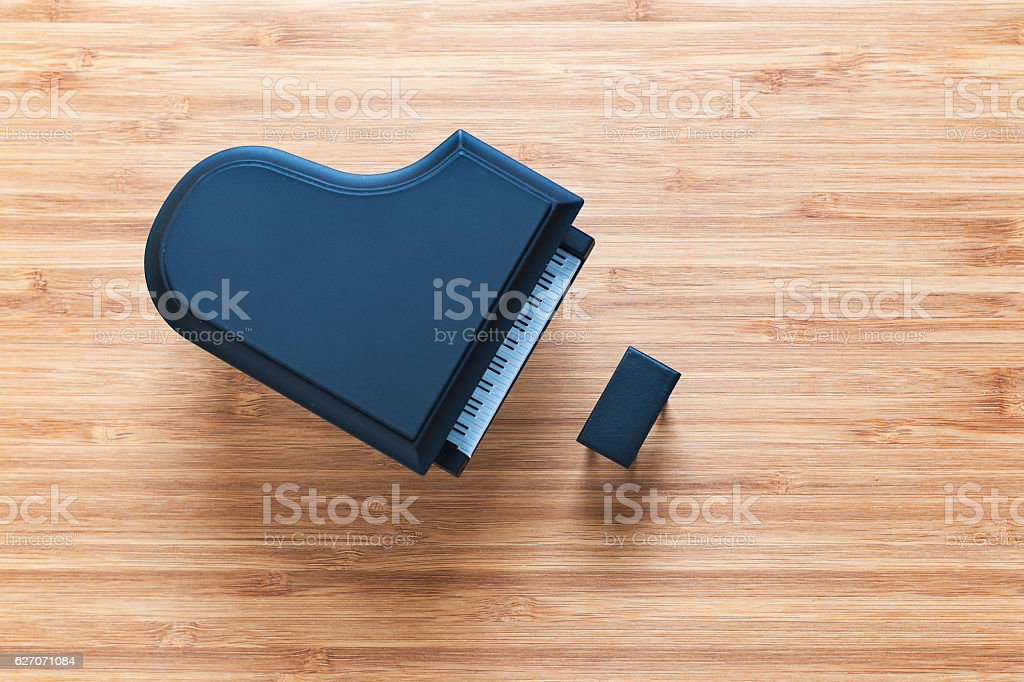 Black toy grand piano on a wooden floor with stool stock photo