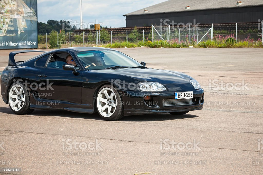 Black Toyota Supra goes down the street stock photo