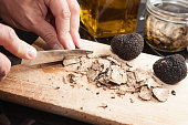 Black truffle and knife on wooden background