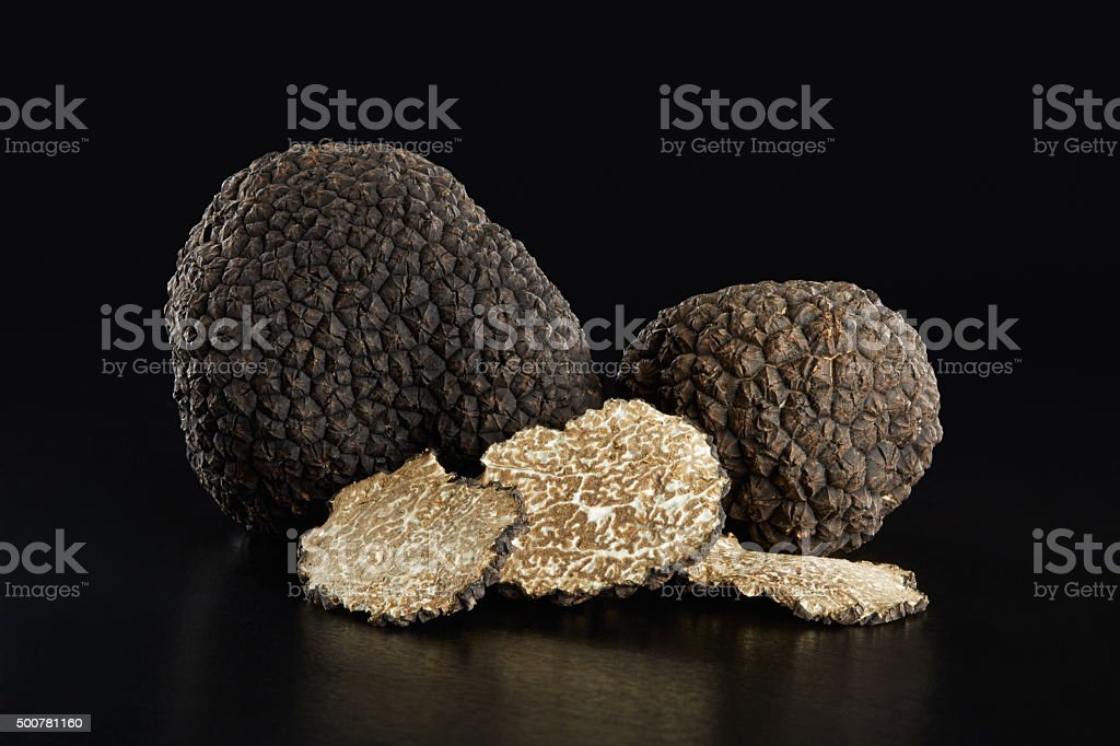 Black truffles and slices on black stock photo