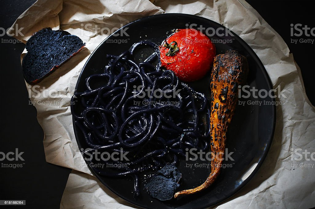 Black udon noodles, pasta with squid ink, tomato and carrot stock photo