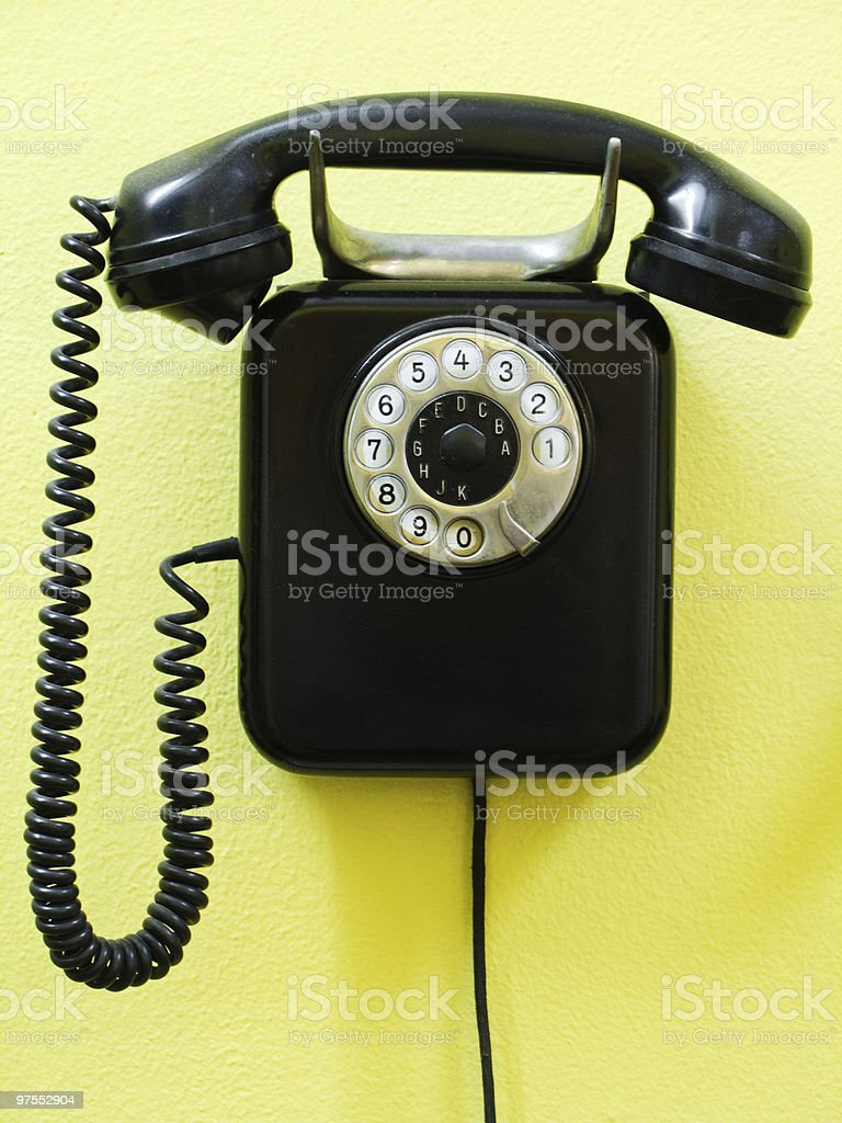 A black vintage phone on a yellow wall royalty-free stock photo