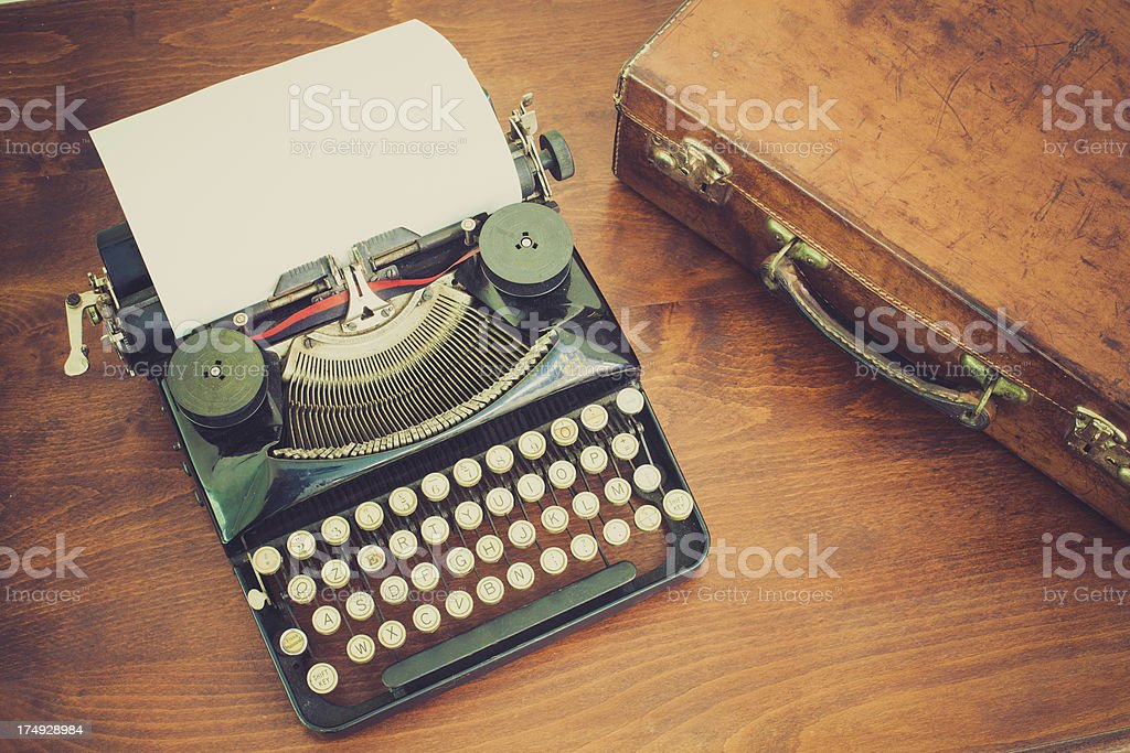 Black Vintage Typewriter with White Sheet of Paper and Briefcase royalty-free stock photo