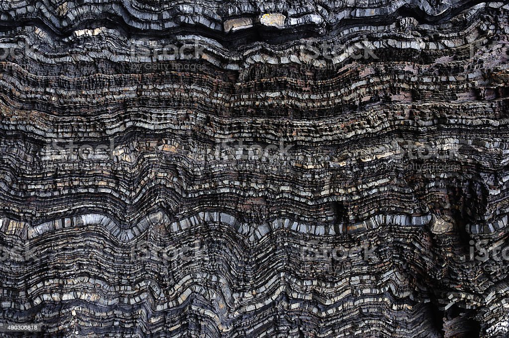 Black wavy layers of rock stock photo