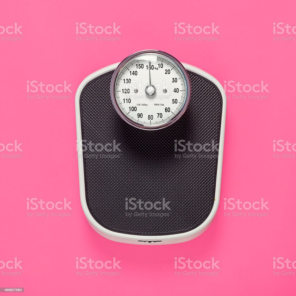Black weighing scales on pink background stock photo