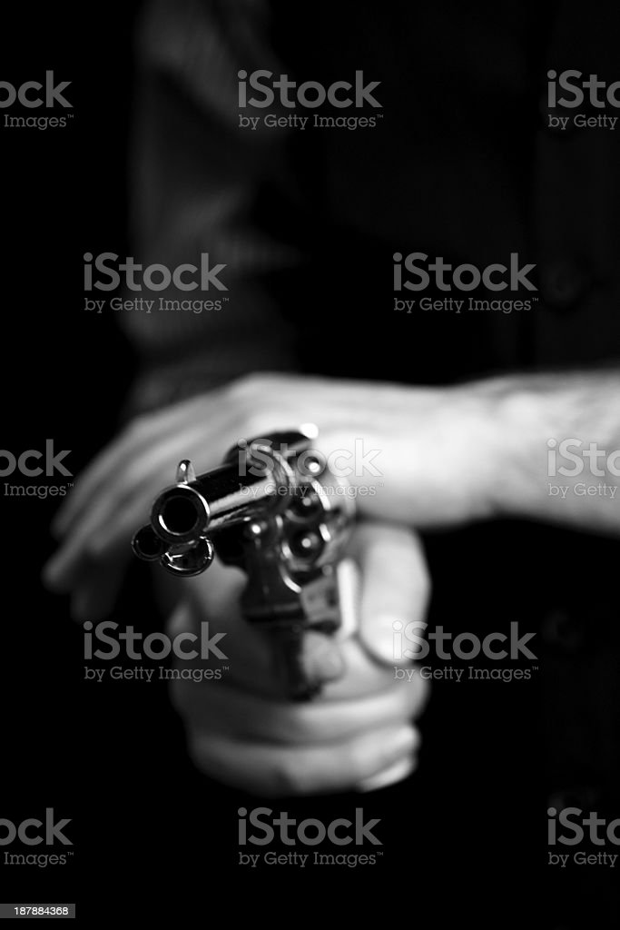 black & white close-up of cowboy holding peacemaker gun stock photo