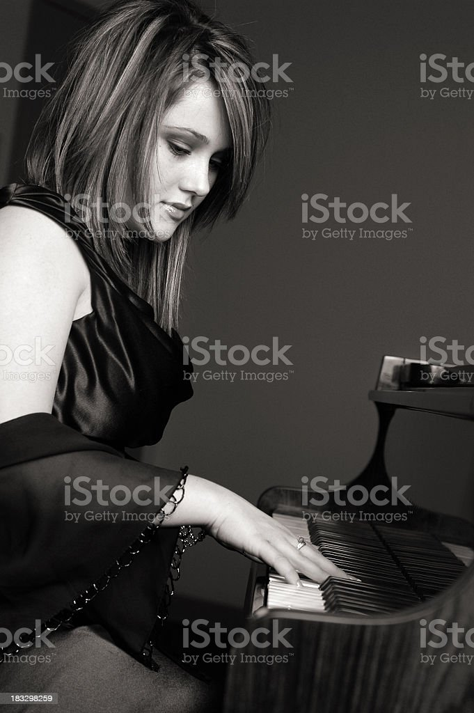 Black & White Image of Teen Girl Playing Piano royalty-free stock photo