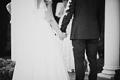 black white photo hands of bride and groom during oath
