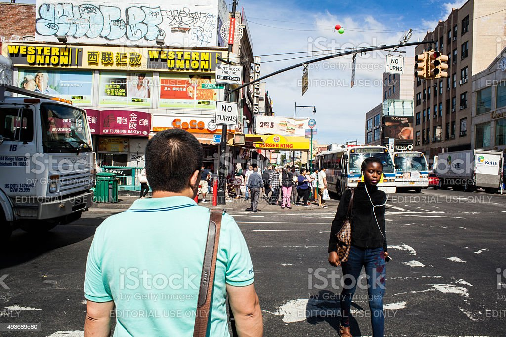 Black Woman crossing Main Street in Flushing Queens' Chinatown stock photo