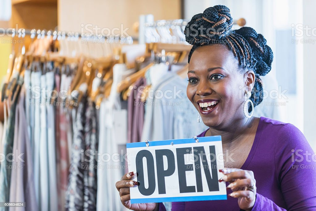 Black woman holding OPEN sign in clothing store stock photo