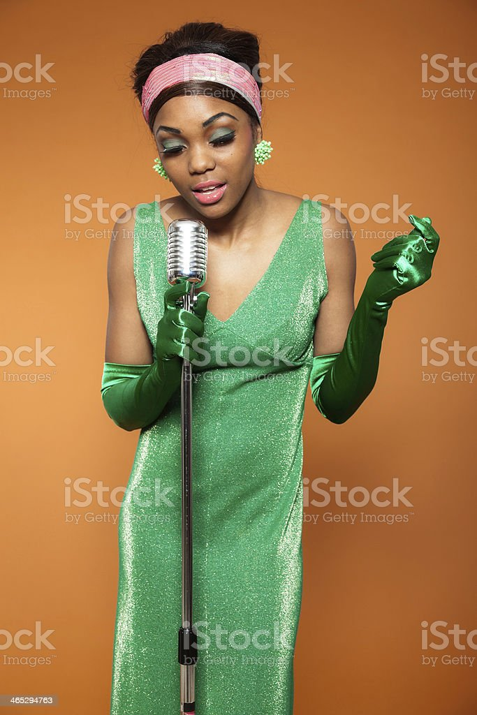 A black woman in a green dress singing soul funk music  stock photo