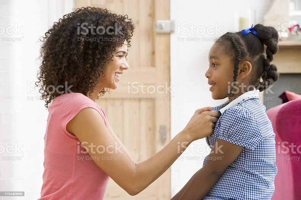 Black woman in front hallway fixing young girls dress stock photo