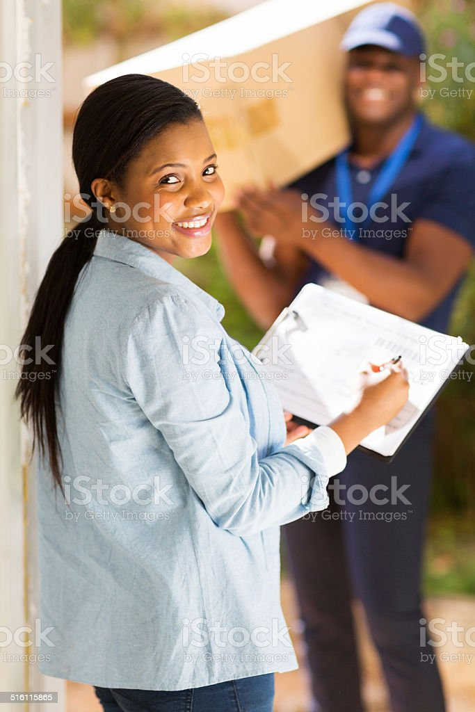 black woman signing document for receiving package stock photo