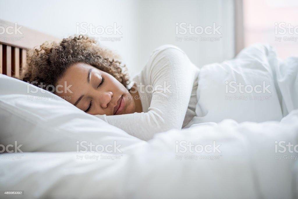 Black woman sleeping in bed stock photo